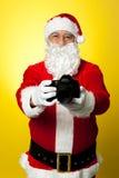 Papá Noel que soporta su DSLR a estrenar Imagen de archivo