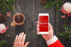 Papá Noel que sostiene el teléfono elegante con el mensaje de la Feliz Navidad en té caliente de la pantalla y de la bebida Fotos de archivo libres de regalías