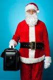 Papá Noel que sostiene la cartera a estrenar foto de archivo