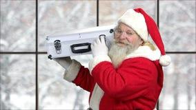 Papá Noel que sostiene porciones de dinero en caso de que almacen de video