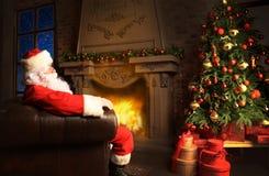 Papá Noel que tiene un resto en una silla cómoda cerca de la chimenea en el país Imagen de archivo libre de regalías