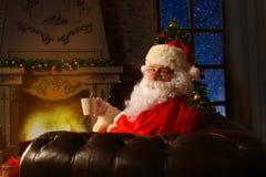 Papá Noel que tiene un resto en una silla cómoda cerca de la chimenea en el país Imagen de archivo