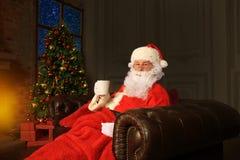 Papá Noel que tiene un resto en una silla cómoda cerca de la chimenea en el país Imágenes de archivo libres de regalías