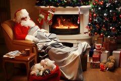 Papá Noel que tiene un resto en una silla cómoda cerca de la chimenea en el país Foto de archivo