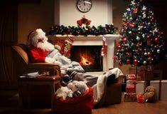 Papá Noel que tiene un resto en una silla cómoda cerca de la chimenea en el país Foto de archivo libre de regalías