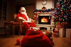 Papá Noel que tiene un resto en una silla cómoda cerca de la chimenea en el país Fotos de archivo