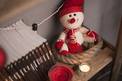Papá Noel se está colocando en un estante con las guirnaldas y las velas Fotografía de archivo