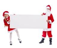 Papá Noel y ayudante que muestran la muestra en blanco Foto de archivo libre de regalías