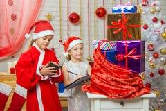 Papá Noel y bolso comprobado ayudante con los regalos Fotos de archivo