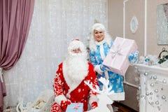 Papá Noel y doncella de la nieve de la nieta con los regalos en el Año Nuevo en un interior festivo ` S del Año Nuevo y la Navida Fotos de archivo libres de regalías