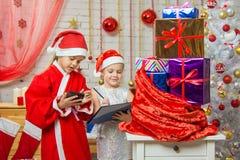 Papá Noel y el ayudante encuentran los regalos en un bolso Fotos de archivo libres de regalías
