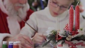 Papá Noel y imagen del drenaje del niño pequeño en el fondo borroso de dos velas festivas almacen de video