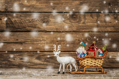 Papá Noel y muñeco de nieve en un trineo del reno con los regalos Imagenes de archivo