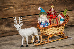 Papá Noel y muñeco de nieve en un trineo del reno con los regalos Imagen de archivo