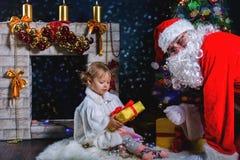 Papá Noel y muchacha que juegan cerca de la chimenea, árbol de navidad adornado Imagen de archivo
