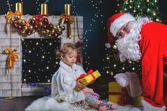 Papá Noel y muchacha que juegan cerca de la chimenea, árbol de navidad adornado Fotos de archivo