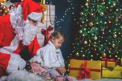 Papá Noel y muchacha que juegan cerca de la chimenea, árbol de navidad adornado Imagen de archivo libre de regalías