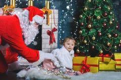 Papá Noel y muchacha que juegan cerca de la chimenea, árbol de navidad adornado Foto de archivo libre de regalías