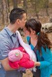 Papá que besa la frente de la mamá y que detiene al bebé Imagen de archivo libre de regalías