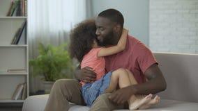 Papá que detiene a su pequeña hija en el revestimiento que la abraza suavemente, paternidad consciente metrajes