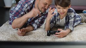 Papá que intenta ayudar al hijo en el funcionamiento con la palanca de mando, la ayuda y el cuidado del videojuego almacen de metraje de vídeo