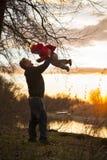 Papá que juega con el bebé en puesta del sol imagen de archivo