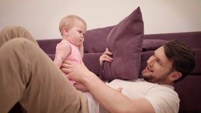 Papá que juega con el bebé en el sofá Padre Time Papá e hija alegres almacen de metraje de vídeo