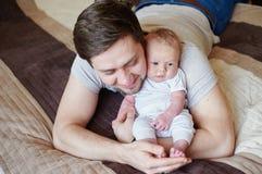 Papá que juega con su hijo en la cama Concepto de familia feliz Fotos de archivo