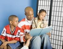 Papá que lee a sus cabritos Fotografía de archivo