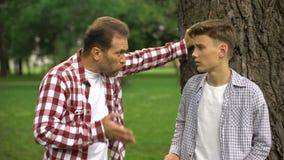 Papá que regaña a su hijo para el malos comportamiento, proceso de la educación, padres y niños metrajes