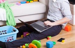 Papá que se sienta en el piso y las aplicaciones un ordenador portátil Fotos de archivo