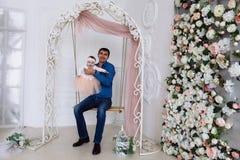 A papá rola sua filha pequena em um balanço em um vestido macio bonito O bebê ri, ela gosta de tudo ao redor foto de stock royalty free