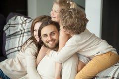 Papá sonriente que mira la cámara que goza de la esposa de los niños que abraza el fathe Fotografía de archivo libre de regalías