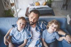 Papá Wailful que abraza a niños en el sofá Fotos de archivo libres de regalías