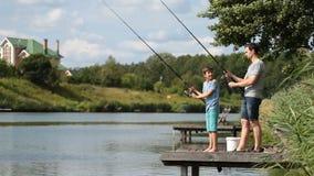 Papá y adolescente que pescan con caña junto en el lago almacen de video