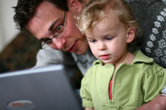 Papá y bebé en el ordenador imagen de archivo