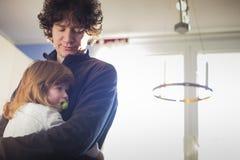 Pap? y beb? que abrazan en casa fotografía de archivo