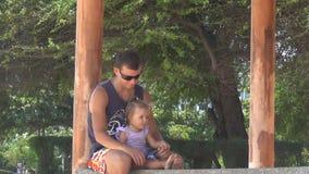 Papá y bebé que juegan en el gazebo por el mar pies el pisar fuerte de la muchacha El papá guarda las piernas de la hija Están ri almacen de video