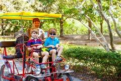 Papá y dos muchachos del niño biking en la bicicleta en parque zoológico con el animal Foto de archivo libre de regalías