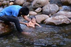 Papá y natación sonriente del muchacho en el río imagenes de archivo
