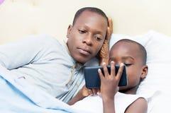 Papá y niño en cama Imagenes de archivo
