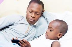 Papá y niño en cama Foto de archivo