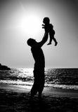 Papá y niño en la playa en la puesta del sol Imagenes de archivo