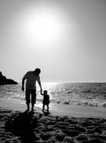 Papá y niño en la playa en la puesta del sol Imágenes de archivo libres de regalías