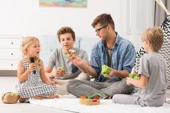 Papá y niños que juegan con las marionetas del finger imagenes de archivo
