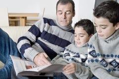 Papá y niños que leen la revista Imágenes de archivo libres de regalías