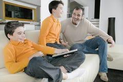 Papá y niños que ven la TV