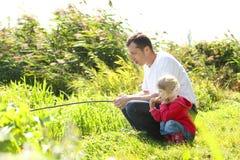 Papá y pequeña hija cerca de un lago Fotografía de archivo