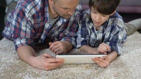 Papá y su hijo que aprenden cómo utilizar la nueva tableta, tecnología moderna, proximidad almacen de metraje de vídeo