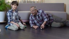 Papá y su hijo que juegan con los coches del juguete en el piso, tiempo agradable junto almacen de metraje de vídeo